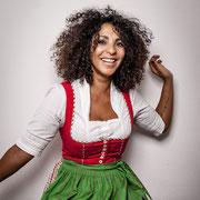 Eine Frau im Dirndl und dunklen, sehr lockigen Haaren tanzt und lacht.