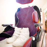Auf der Sitzfläche eines Rollstuhls steht ein paar Schuhe.
