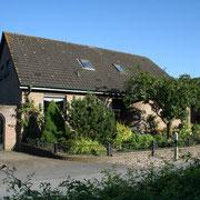 4. Bild: Vorderansicht mit linker Haus-Seitenansicht und Gästeparkplatz.