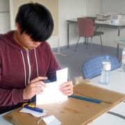 Ein Projektmitarbeiter bei der Vorbereitung des Produktstandes - er schneidet die Flyer passend zu; dabei arbeitet er konzentriert und genau.