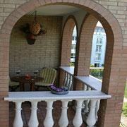 Balkon überdacht mit Tisch und 2 Stühlen
