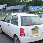Werbung für Sonnenenergie. Auf dem Parkplatz lassen die meisten Japaner ihre Autos bei laufendem Motor stehen, oft mehr als 15 Minuten.