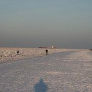 Einsame Spaziergänger am verscheiten Strand von Duhnen