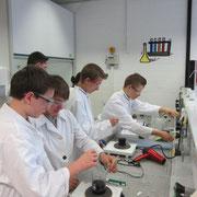 Schüler beim Experimentieren: vorne Färben von Stoff mit Indigo (typischer Jeans-Farbstoff), hinten mit Berliner Blau.