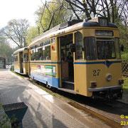 Der Zug bestehend aus dem Gotha-Triebwagen Nr. 27, und dem Beiwagen Nr. 90, beide Baujahr 1960, an der Endstation beim S-Bahnhof Rahnsdorf,  wartet auf Passagiere, die von der S-Bahn kommen. Der Triebwagen hat eben gerade die Seite gewechselt.