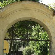 Der (zu renovierende) barocke Torbogen mit geschweiftem Giebel und schmiedeeisernem Laub- und Bandelwerk