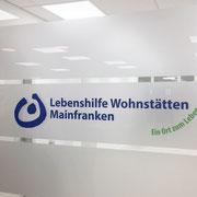 Sichtschuztbeklebung in Büro auf Glastrennwand mit aufgesetztem Firmenlogo
