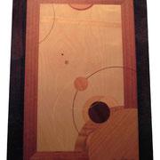 ●タイトル:「宙-ひろがり-」 ●サイズ:485×705×18mm ●コメント:バックの板の木目にすいこまれそうなブラックホールをイメージしました。細い円を交差させるのに苦労しました。