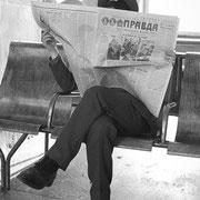 駅構内で新聞を読む人