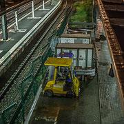 Extérieur nuit, pluie. Chemins de fer et tracteur électrique jaune. Gare ferroviaire Saint-Jean, Bordeaux