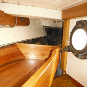 starboard - porthole opening into cockpit - storage shelf