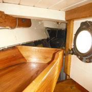 starboard - porthole opening into cockpit - storage shelf