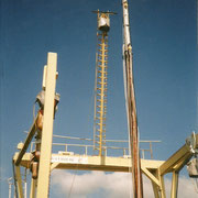 The mast being positioned by the crane