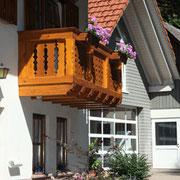 Landhausbalkon, vorgehängte Balken, geschnitzte Blumenkästen