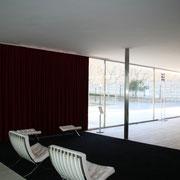白いバルセロナ・チェアに真紅のカーテンが映える