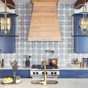 Beautiful blue cabinets and tiles play together perfectly and accentuate that lovely maple hood.