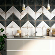 A bold, graphic zig-zag is softened by the worn appearance of these porcelain tiles.