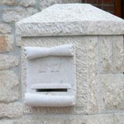 Buzón tallado sobre pilastra maciza