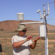 Paraecologist maintaining automatic weather station in South Africa.