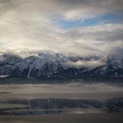 Der Hopfensee im Winter mit Blick auf die verschneiten Alpen
