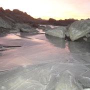 Viele klein Wasserlachen gefrieren über Nacht. Tagsüber wärmt die Sonne und lässt kleine Bächleine über den Gletscher fliessen.