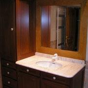 Agencement d'un mobilier de salle de bain réalisé en bois d'acajou. Miroir chauffant en bois de merisier. Boutons de tiroir en porcelaine. Plan de vasque en marbre.