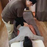脚をクロスさせながら腰部を緩めて腰痛の緩和をしています。