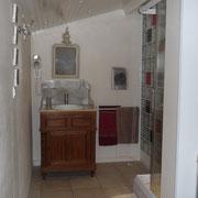 Salle d'eau avec radiateur d'appoint et sèche-cheveux, donnant sur la chambre