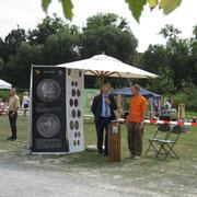 im Gespräch mit Bm Olma; im Hintergrund die Aussteller mit großformatigen Abbildungen der gezeigten Münzen