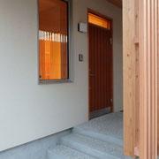 洗い出し仕上げのアプローチと木製玄関ドア