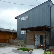 ガルバリウム鋼板外壁と木板を使った玄関アプローチ
