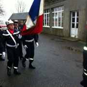 défilé vers le monument aux Morts derrière le drapeau