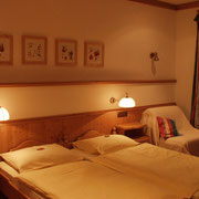 Gemütliches Doppelzimmer in rustikalem Stil in freundlichen, hellen Farben.