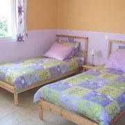 la chambre avec deux petits lits du Gite des Tournesols - aux Gites des Camparros à Nailloux