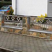 Edelstahl-Zaunelemente in einer Steinmauer eingefasst
