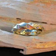 gedrehter Gelbgoldring mit gestreuten Brillanten
