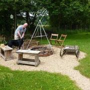 Christof installiert das Dreibein über der Feuerstelle inklusive Aufhängung für den Grill