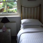 Chambre secondaire de la maison. Avec lit un place et vue sur le jardin.