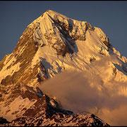 Ein Nebengipfel der Annapurna im roten Licht des Sonnenaufgangs.