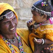 Junge Mutter mit Kind in traditioneller Bekleidung.