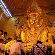 Auf eine Buddhastatue wird von Gläubigen Blattgold aufgelegt.