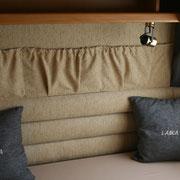 parete posteriore con paretina  anticondensa ricoperta e con tasche portaoggetti-portariviste e cuscini con ricamo laika. Camper laika. By ballabioiltappezziere.com