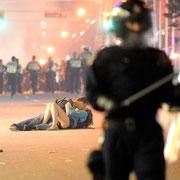 Фотография была сделана во время беспорядков, устроенных хоккейными болельщиками в канадском Ванкувере.