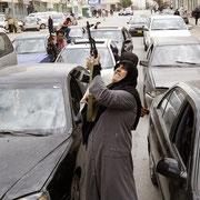 Женщина-участник сопротивления салютом приветствует отступление войск Муаммара Каддафи от Бенгази и начало операции международных сил в Ливии.