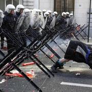 Демонстрант показывает свой зад полицейским во время акции протеста представителей профсоюзов и рабочих, которые требуют защиты рабочих в странах ЕС, Брюссель, 24 марта.