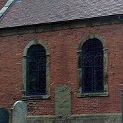 18th-century windows cut out of the original stone building now encased in brick