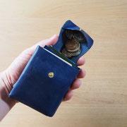 フタの両側を握り、財布を傾けて小銭を出します。