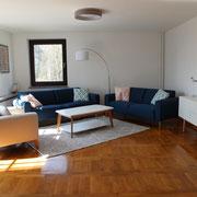 Blick ins Wohnzimmer mit zwei komfortablen Sofas und einem Sessel