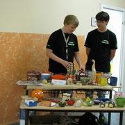 Paul und Kevin sortieren den Verkaufsstand neu und setzen jedes einzelne Produkt in Szene