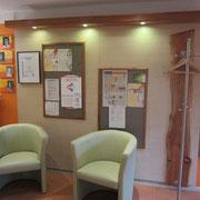 Praxiswartezimmer Bereich mit Infotafeln u Mantelgarderobe in Kirsch u Ahorn